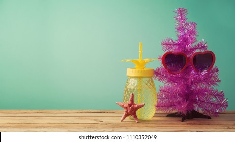 Christmas in July concept with funny Christmas tree, sunglasses and pineapple jar on table background