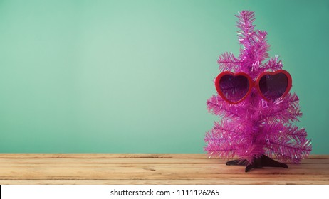 Christmas in July concept with funny Christmas tree and  sunglasses on table background