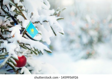 Christmas Kazakhstan. Xmas tree covered with snow, decorations and a flag of Kazakhstan. Snowy forest background in winter. Christmas greeting card.