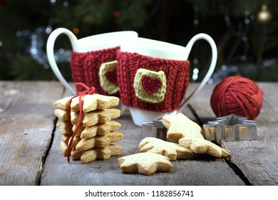 christmas - knitted woolen cups and star shaped gingerbread on a wooden table