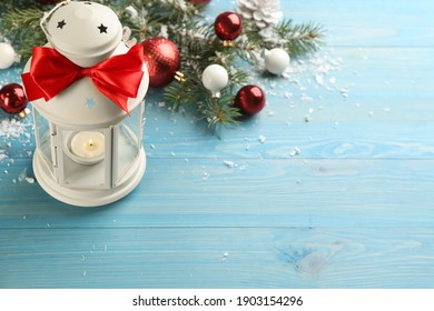 Christmas lantern with burning candle and festive decor on light blue wooden table. Space for text