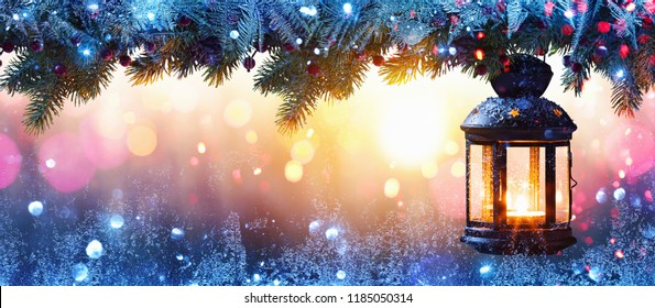 Christmas Lantern On Snow With Fir Branch in the Sunlight. Winter Decoration Background