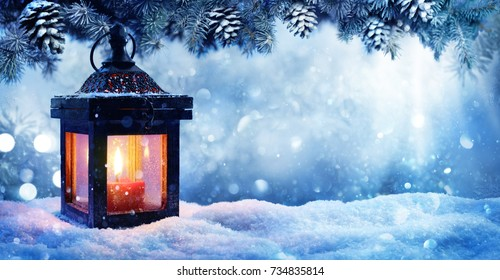 Photo of Christmas Lantern On Snow With Fir Branch In Evening Scene