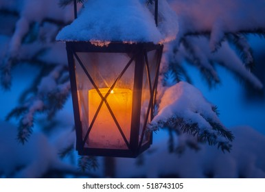 Christmas lantern with snow and candle