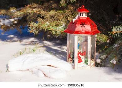Christmas lantern with snowfall near green fir tree