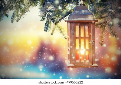 Christmas lantern in sunset light. Blur snowy background. Copyspace for text