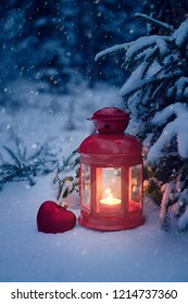 Christmas lantern under the tree with a toy heart in the forest