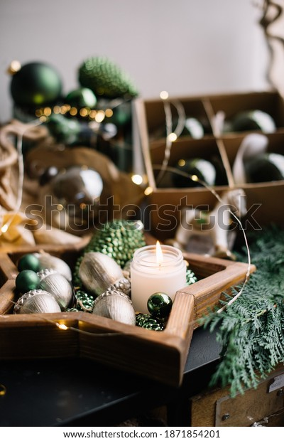 Christmas layout: green and silver coloured ornaments and baubles in stars, acorns and pine cones shapes, pine branch and a cute burning candle in the star shaped wooden tray, close up view