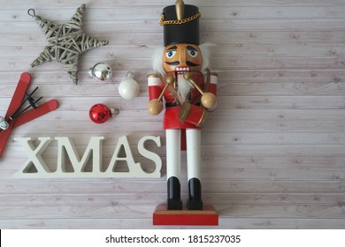 Christmas layout in red and white against wooden background, Christmas beads garlands, balls, wooden letters, nutcracker, flat lay, copyspace