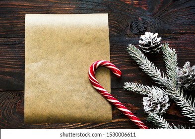 Christmas layout, spruce branch with cones, with snow, candy, new year congratulations on  dark wooden dackground, make a wish, letter to Santa.  Flat lay, top view, copy space for text.