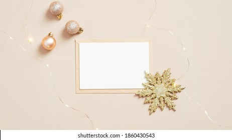 Christmas letter concept. Blank paper card, envelope, balls decoration and golden snowflake on pastel beige background. Flat lay, top view.