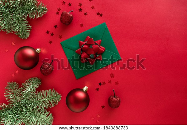 Christmas letter with greeting card and congratulations, christmas tree branches, baubles, glitter decorations on red surface. Merry Christmas happy New Year concept. Flat lay from above, copy space