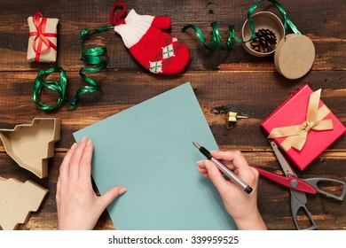 Christmas letter writing on blue paper on wooden background with decorations