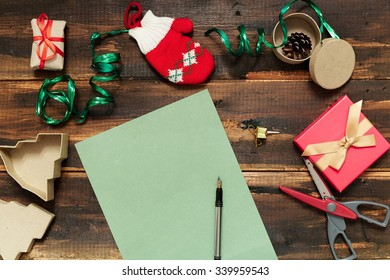 Christmas letter writing on green paper on wooden background with decorations