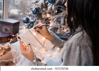 Christmas letter writing on notebook. Many garlands. Christmas , winter holidays and people concept. Letter to Santa Claus. Girl writes her wish