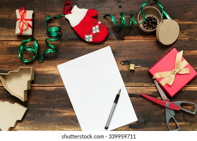 Christmas letter writing on white paper on wooden background with decorations