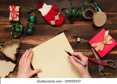 Weihnachtsschreiben auf gelbem Papier auf Holzhintergrund mit Dekoration