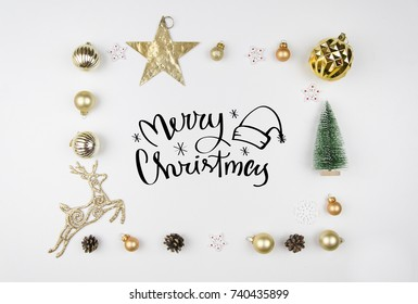 Christmas lettering. Frame made of christmas decoration, Christmas deer, balls, cones, golden star and fir tree. Flat lay, top view. Trendy greeting card modern calligraphy
