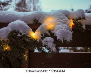 Christmas light decoration over balcony railing under snow cover in daylight and overcast