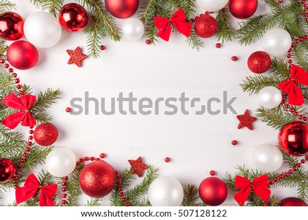 Christmas light frame decorated with red and white baubles, bows and fir branches. Copy space in the center