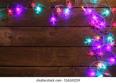 Christmas lights background. Holiday shiny garland border top view on brown wooden planks surface. Xmas tree decorations, winter holidays illumination