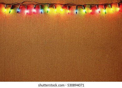 Christmas lights border and frame on wooden background.