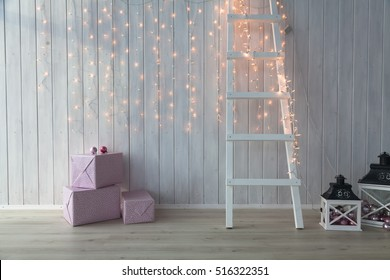 Christmas lights burning on a white wooden background with pink giftboxes and stairs.