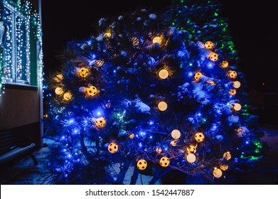 Christmas lights in the form of soccer balls shine at night in the yard. Christmas tree decorated with yellow and blue lights, closeup.