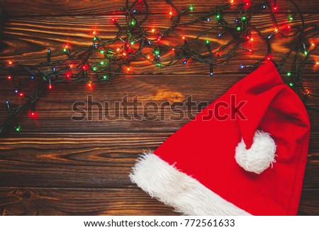 Christmas Lights In A Frame On Rustic Wooden Table Near Santa Claus Hat Merry