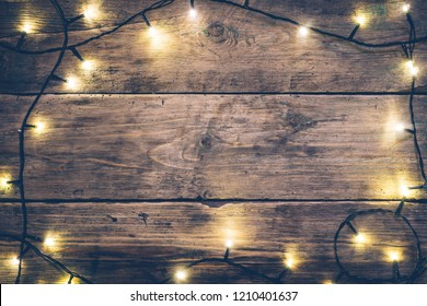 Christmas lights frame. Christmas wooden rustic background with (decorated) christmas lights. Copy space. Top view. Christmas mood, comfort.