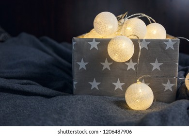 Christmas lights garland with round white lanterns in a gray box on gray background.  Preparing for Christmas and New Years concept. Apartment decoration