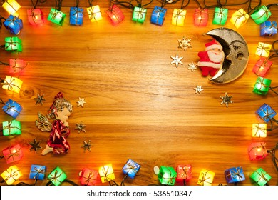 Christmas lights gift box frame,santa and angel on golden wood background.decoration. or New Year concept.with copy space for your text