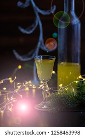Christmas lights and glass with limoncello drink on dark wooden background