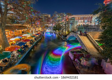 Christmas Lights illuminated San Antonio downtown River Walk with Restaurants on side and boats on the river in Texas, USA