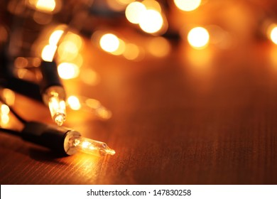 Christmas lights on dark wooden background