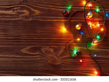 Christmas lights and small colored balls on wooden background with copy space