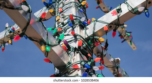 Christmas lights strewn around an iron pole in complete dissarray.