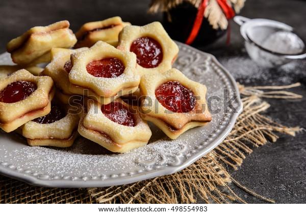 Weihnachtsleinzer-Kekse mit Erdbeermarmelade gefüllt