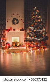 Christmas living room with fireplace, festive illumination. Xmas lights, candles, christmas tree shiny decorations and garlands. Modern interior design, winter holidays magic night atmosphere.