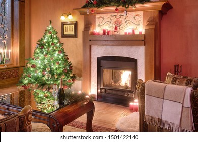 Christmas living room interior with fireplace and armchairs. Christmas tree, garlands, champagne