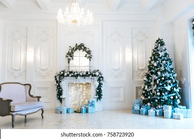Christmas living room with a Christmas tree, fireplace, gifts and a large window. Beautiful New Year decorated classic home interior.