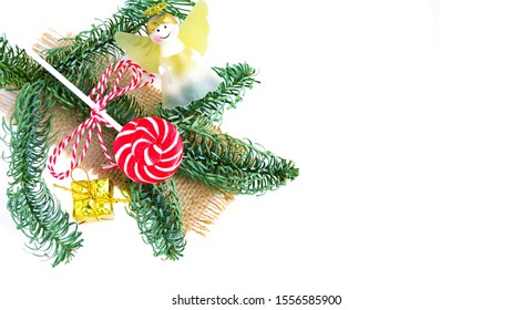 Christmas lollipop, golden gift, angel and ?hristmas tree branch on white. Copy space. Flat lay. New Year and Christmas sweets