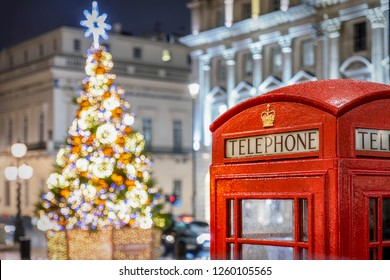 Christmas in London: a classic, red telephone booth in front of an illuminated Christmas Tree in Central London, UK, during night time