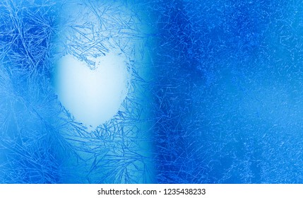 Christmas love heart frozen blue window background. Valentines day greeting card with love shape symbol and ice flowers on transparent glass. Macro view, copy space.