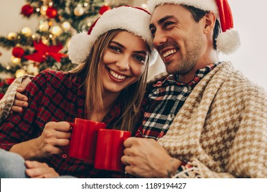 Christmas. Love. Home. Portrait of young couple in Santa hats, covered in plaid holding cups, hugging and smiling while sitting at home near the Christmas tree