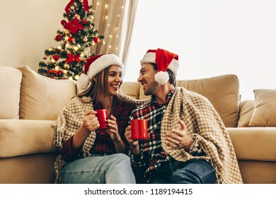 Christmas. Love. Home. Young couple in Santa hats, covered in plaid is holding cups, talking and laughing while sitting at home near the Christmas tree