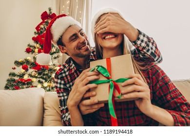 Christmas. Love. Presents. Man is covering his woman's eyes and giving her a gift box. Both are in Santa hats smiling while sitting at home near the Christmas tree