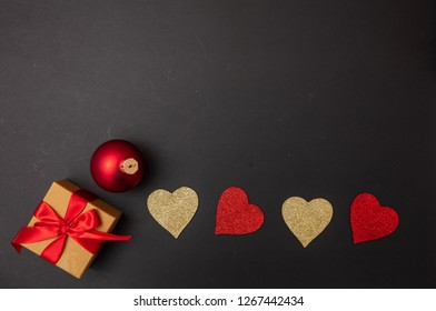 Christmas and love. Top view of red and golden hearts, a gift box with red ribbon and a christmas ball, black background, copy space,