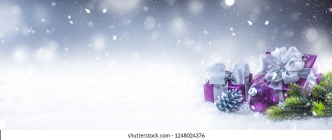 Christmas luxury purple gifts in snow and abstract snoiwy atmosphere.