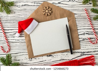 Christmas mail, envelopes with letters on a light wooden table next to a Christmas tree branches, cones and traditional Christmas candies. Winter holidays concept.  Top View